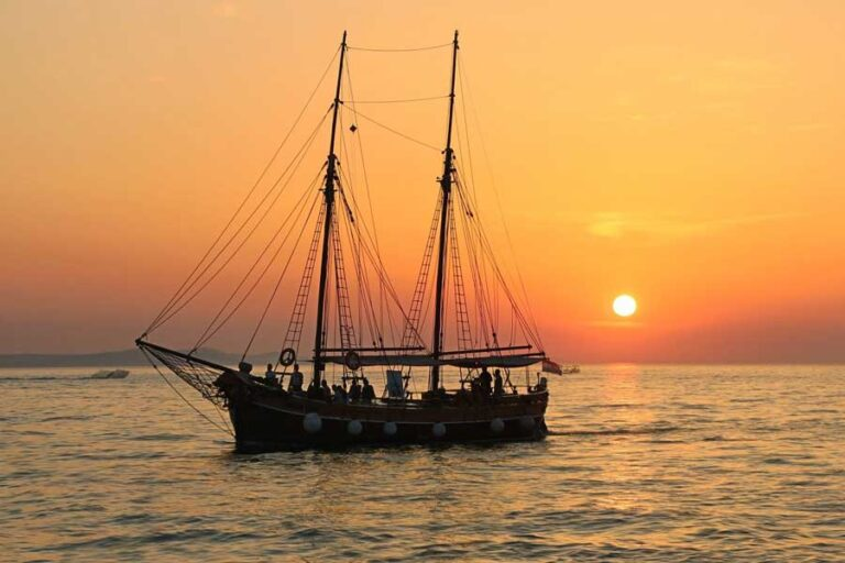 Picture of a sailboat on the water at sunset